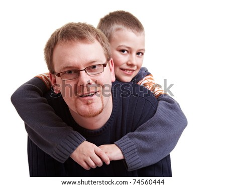 Father giving his happy son a piggyback ride - stock photo