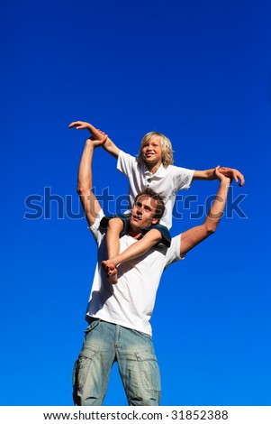 Father giving his son a piggyback ride against the blue sky - stock photo