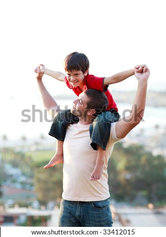 Father giving his son piggyback outdoors - stock photo