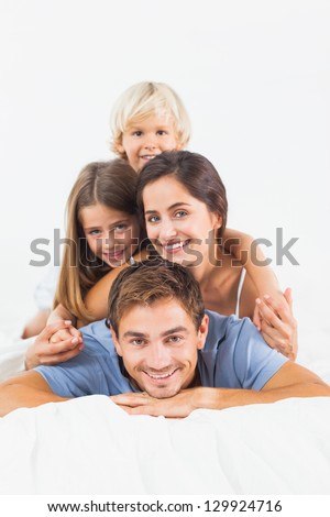 Father giving piggy back to his family on the bed