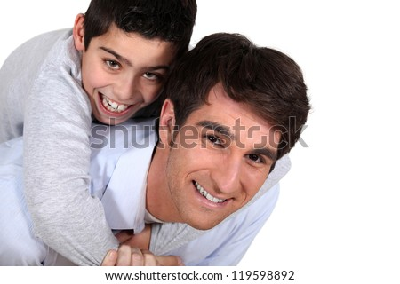Father giving son piggy-back - stock photo