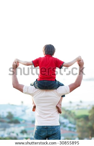 Father giving son piggyback ride outdoors - stock photo