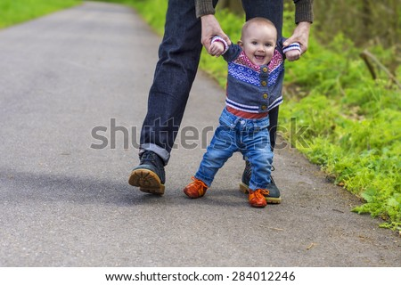 Father guiding his baby with the first steps - stock photo