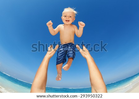 Father hands tossing up the high air joyful baby boy in on white sand sea beach. Outdoors healthy child activity, active lifestyle and having fun on family summer vacation with son on tropical island - stock photo
