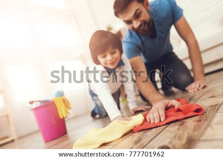 Father has fun with his son. An exemplary father and a boy at leisure. The father shows his son how to clean the house. A man accustoms the boy to cleanliness.