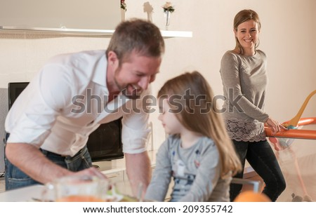 Father having breakfast with his little girl, mother in the background on playpen - stock photo