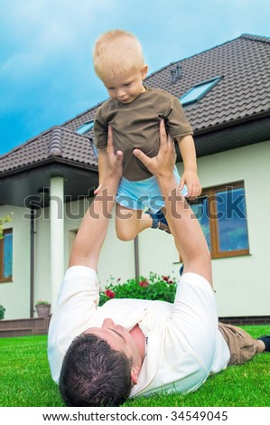 Father having fun with a baby in yard - stock photo