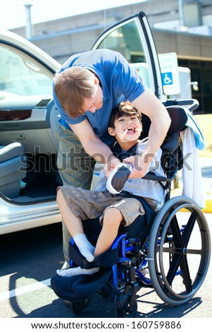 Father helping disabled child in wheelchair. Child has cerebral palsy. - stock photo