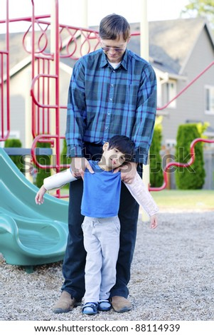Father helping disabled four year old son to play at playground