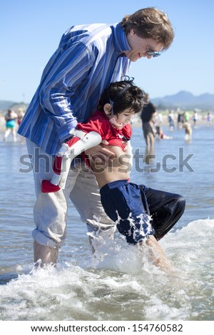Father helping disabled son walk in the ocean waves on beach. Child has cerebral palsy. - stock photo