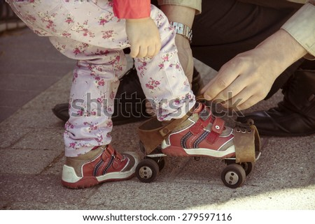 Father helping her little daughter to try on vintage roller skates. Old film photo style. - stock photo