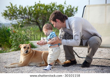 father helping his baby son to communicate with dog - stock photo