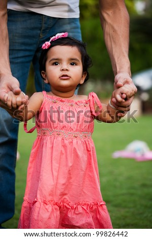 father helping his daughter to take first step of life - stock photo