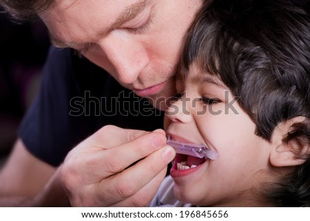 Father helping his disabled son - stock photo