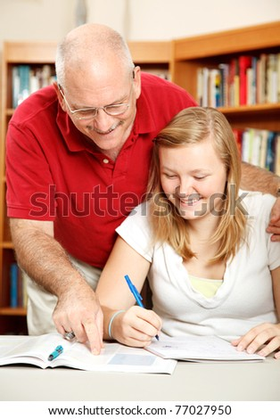 Father helping his teenage daughter study in the library.  Focus on Dad. - stock photo