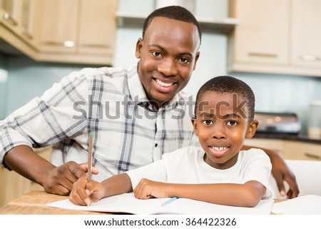 Father helping son for homework in the kitchen