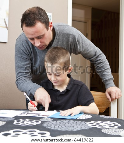 Father helping son with his homework sitting in at the table - stock photo