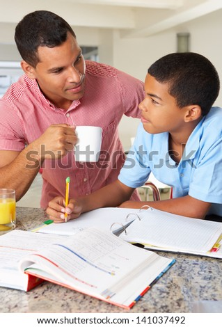 Father Helping Son With Homework In Kitchen - stock photo