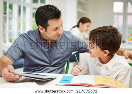 Father Helping Son With Homework Using Digital Tablet - stock photo