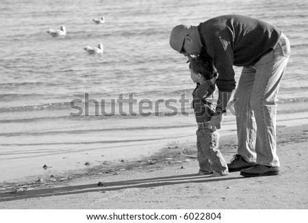 Father Helping Young Son at the Shore - stock photo