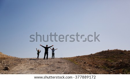 father hiking with two kids in the desert - stock photo