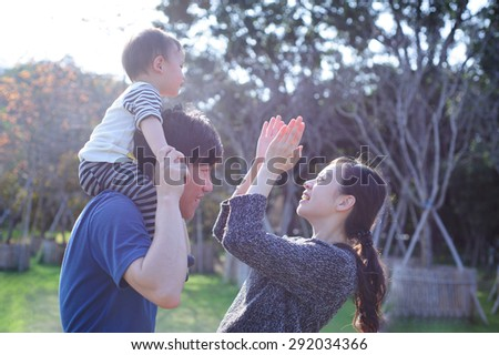 father hold his baby and mother is playing with her baby - stock photo