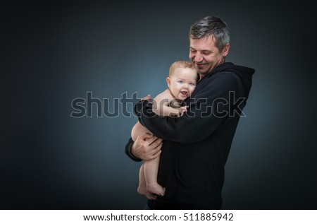 father holding a baby on a dark background