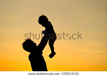father holding and raising his son silhouette - stock photo