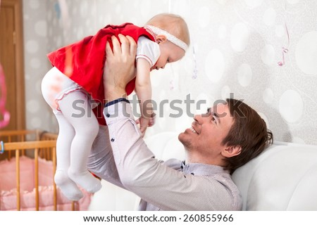 Father holding baby girl on stretched hands - stock photo