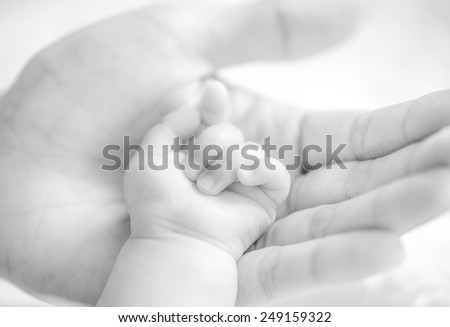 father holding baby hand in black and white filter effect
