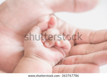 father holding baby hand,soft focus