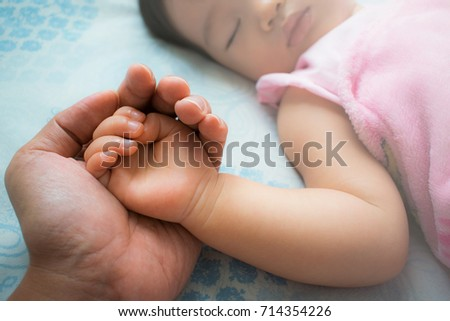 Father holding baby's hands. Father's love.