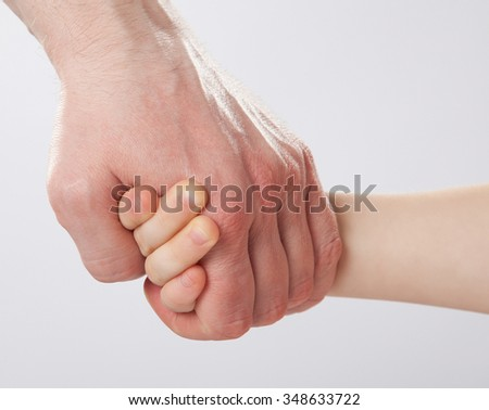 Father holding child's hand, closeup shot on grey background - stock photo