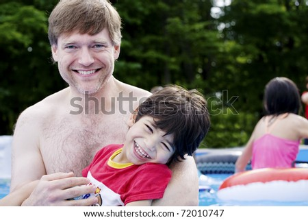 Father holding disabled son in pool - stock photo