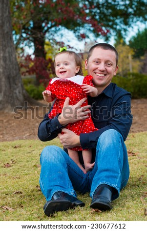 Father holding his baby girl outdoors at park during autumn - stock photo