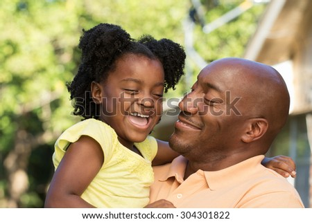 Father holding his daughter and smiling. - stock photo