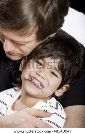 Father holding his disabled son - stock photo