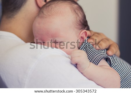 Father holding his newborn baby. - stock photo