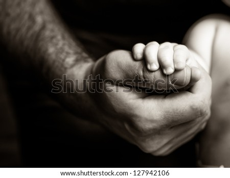 Father holding his son's hand - black and white photography - stock photo