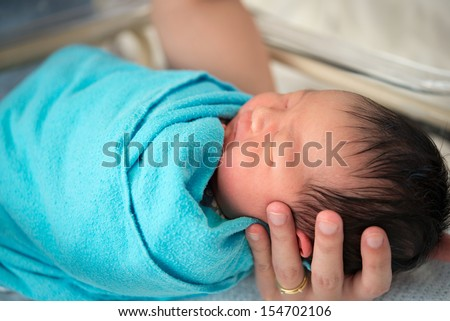 Father holding newborn Asian baby girl, inside hospital room - stock photo