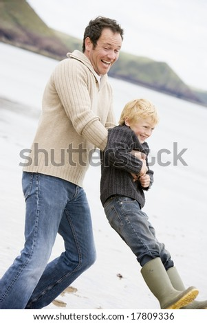 Father holding son at beach smiling - stock photo