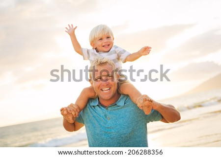 Father holding son on his shoulders on the beach at sunset.
