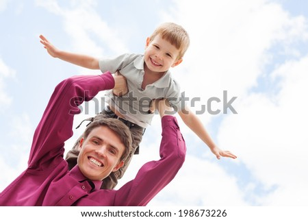 Father holding son showing plane outside - stock photo