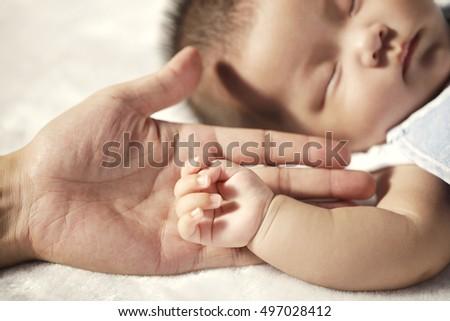 Father holding the hand of baby