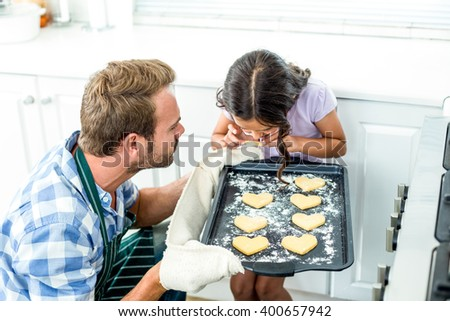 Father holding tray while daughter looking at cookies in kitchen at home - stock photo