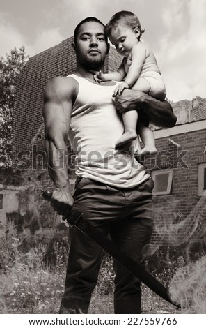 Father hugging a baby and holding a sword, black and white photo. Conceptual photo, parental protection.   - stock photo