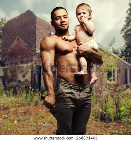 Father hugging a baby and holding a sword. Conceptual photo, parental protection.   - stock photo