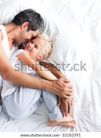 Father hugging her little daughter on bed - stock photo