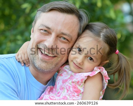 Father hugging his little daughter in nature