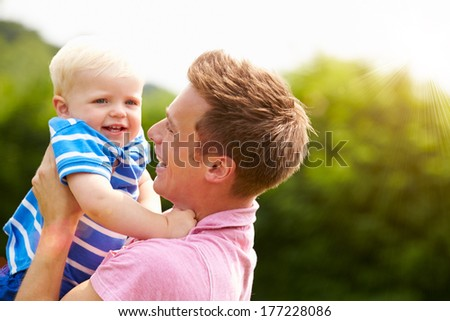 Father Hugging Young Son In Garden - stock photo